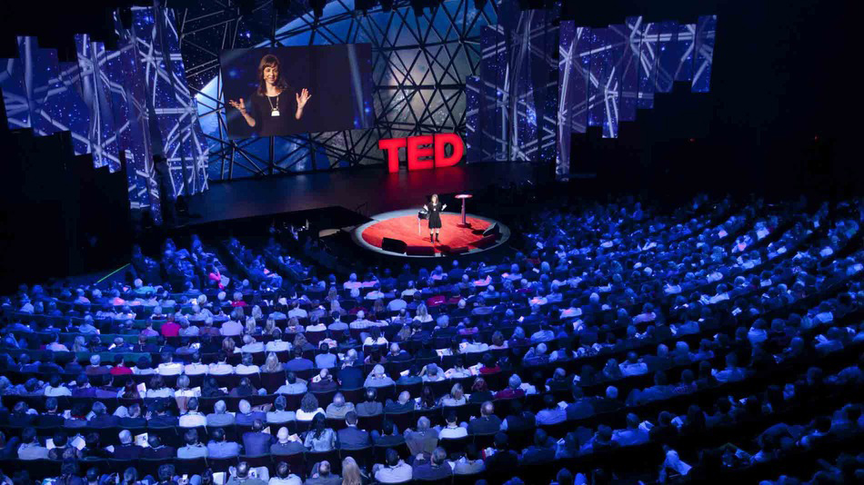 Huge audience with speaker on small stage for TED Talks
