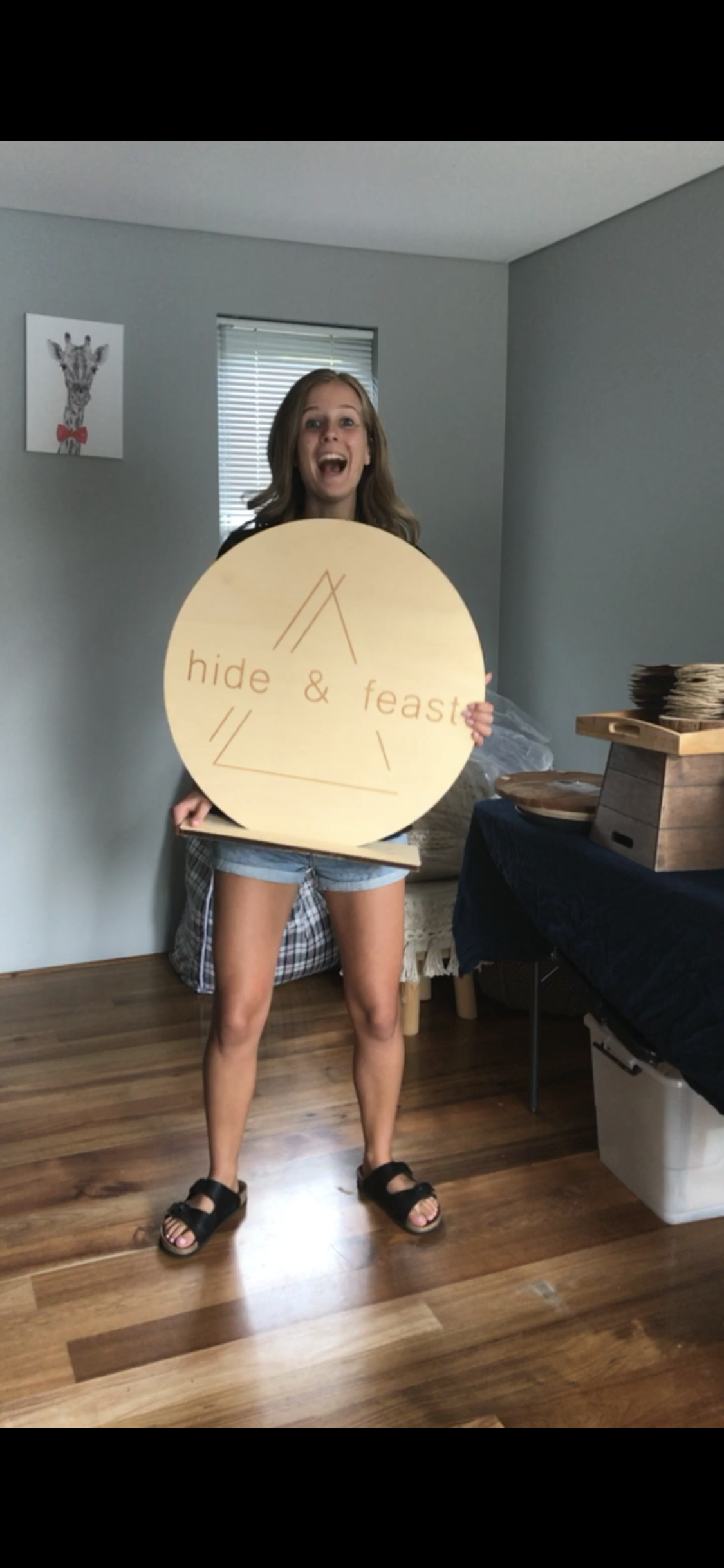 Tess holding her branded signage for Hide and Feast