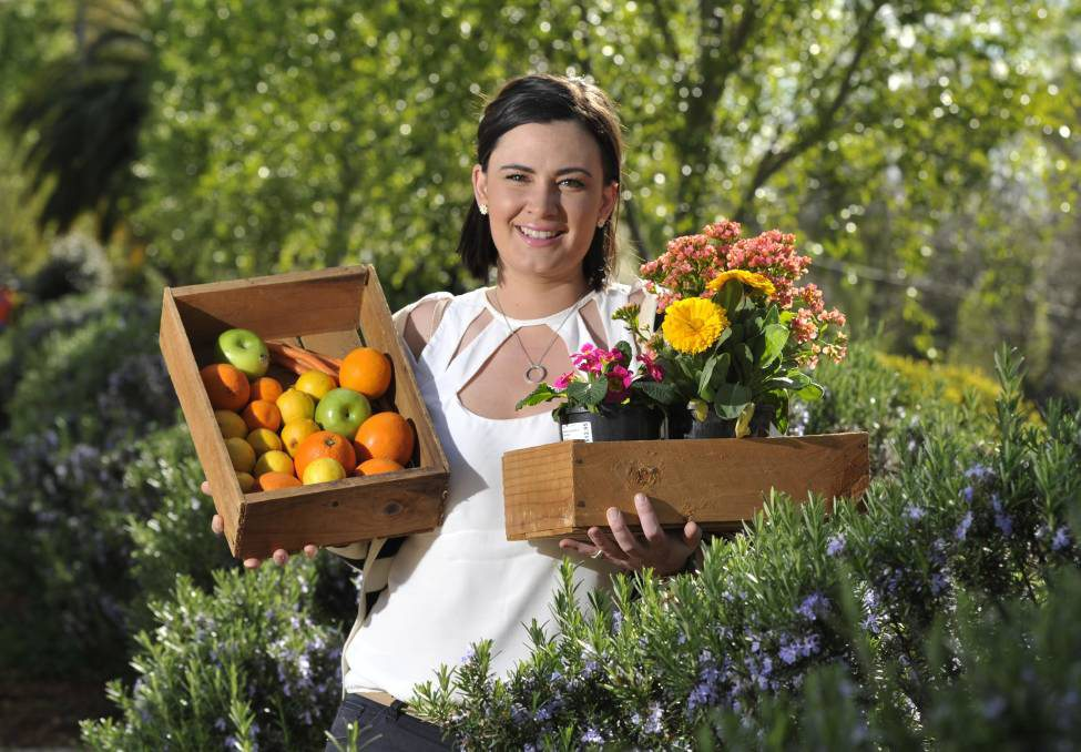 Media shot of Graduate Alex holding boxes of fresh produce for her event