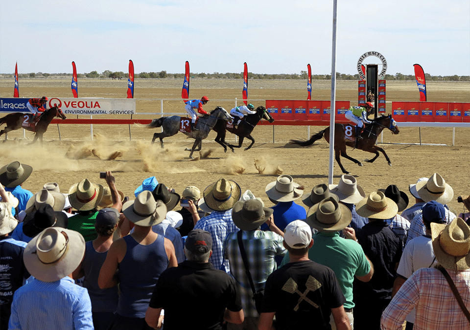 Crowd and horses at the finishing line of the Birdsville Races QLD