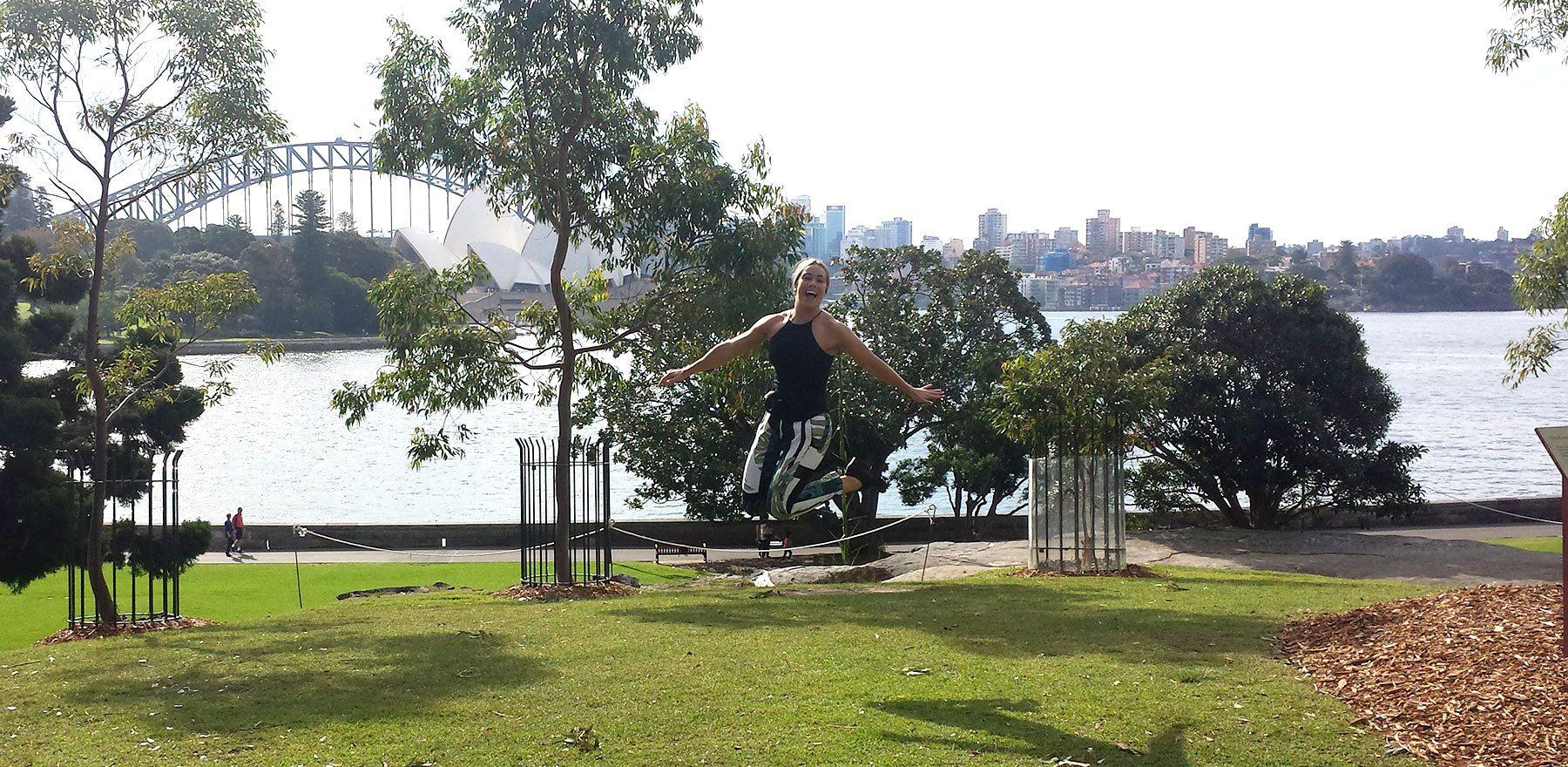Grad Lauren jumping for joy in Botanic Gardens Sydney