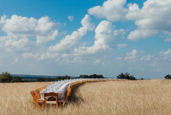 Long lunch table setting in field by Oustanding in the Field